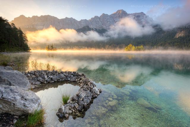 Herbstmorgen am Eibsee | Es wird Herbst am Eibsee am Fuße des Wettersteingebirges mit der Zugspitze als höchsten Gipfel. Nebelschwaden wabern über den See, ständig bildet sich neuer Nebel über dem See, der von den Sonnenstrahlen in ein warmes Licht getaucht wird.