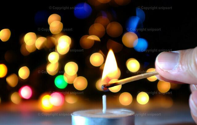 Anzünden eines Teelichts | Ein Teelicht wird mit einem Streichholz angezündet mit Bokeh-Lichtern im Hintergrund.