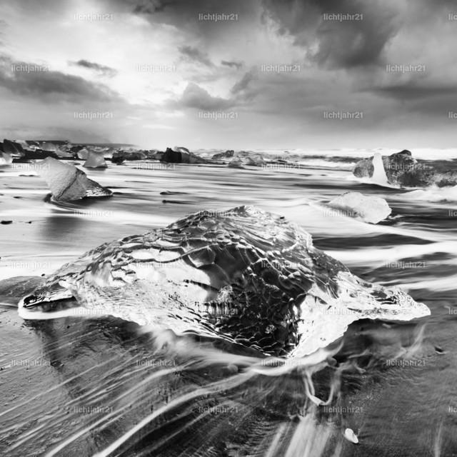 Eisblock am schwarzen Strand | Schwarzweißbild eines markanten Eisblocks an einem schwarzen Strand mit starker Brandung, Bewegungsspuren des abfließenden Wassers auf dem dunklen Sand, im Hintergrund weitere Eisblöcke, Wellen rollen heran, kontrastreicher Himmel - Location: Island, Jökulsarlon (Jökulsárlón)