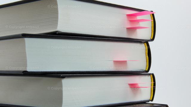 Bücherstapel | Mit Lesezeichen versehene Stellen in mehreren übereinandergestapelten Büchern.