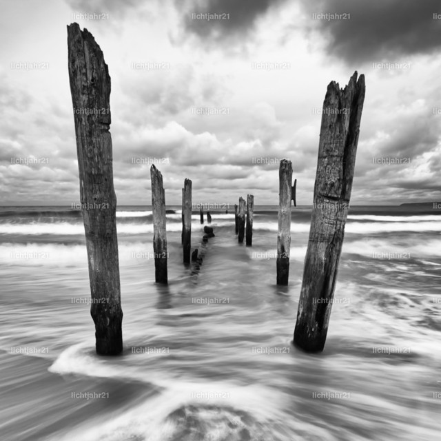 Wooden poles on the beach | Scenic view of wooden poles on a beach, the movement of the waves is shown in addition to a colorful evening sky, black and white version - Location: Baltic Sea, Rügen Island