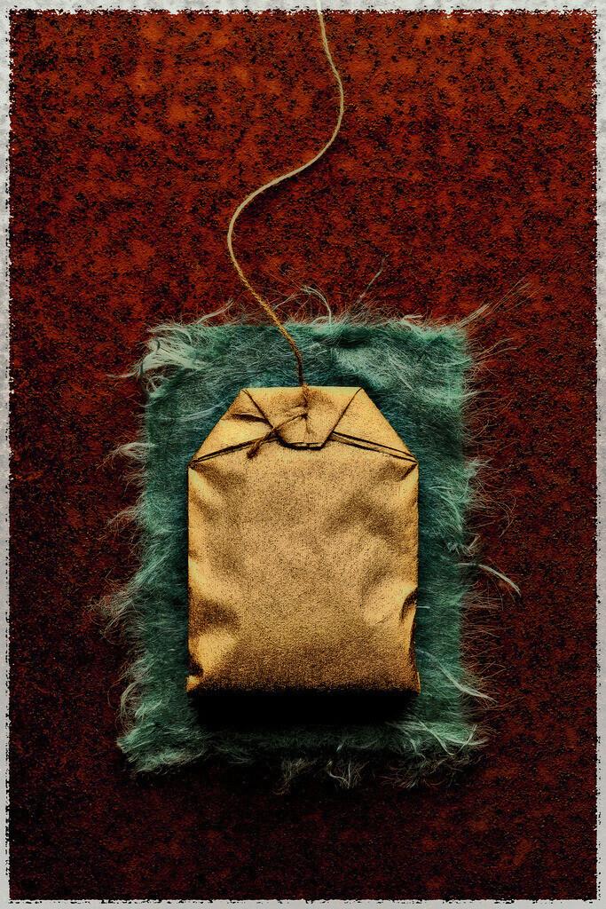 Goldbarren | Goldener Teebeutel auf grünem Filz