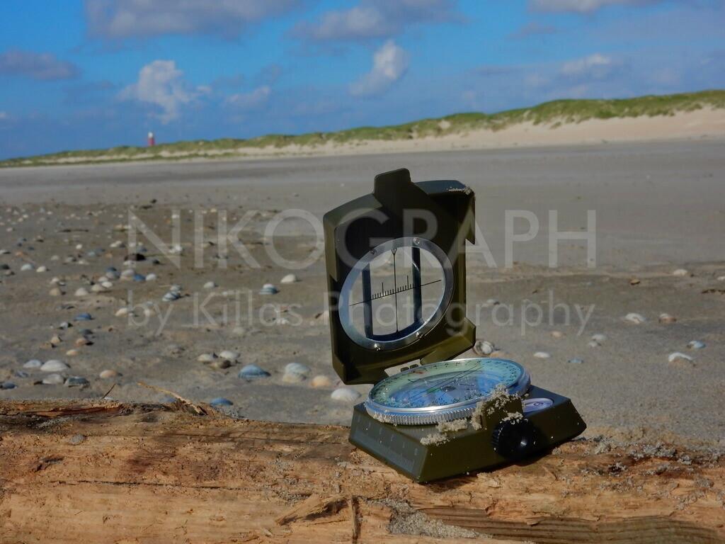 Kompass am Strand   Kompass am Strand bei De Cocksdorp auf Texel. Im Hintergrund ist der Leuchtturm von Texel zu erkennen.
