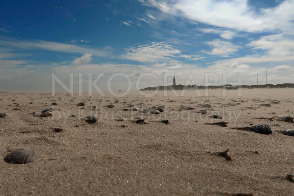 Strand | Der Strand mit dem Leuchtturm der Nordseeinsel Texel unter dem blauen Himmel mit einer schönen Wolkenzeichnung.