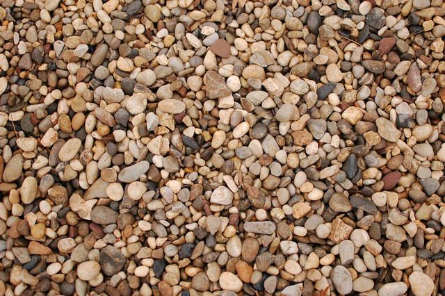 Wassersteine (Hintergrund) | Ein Hintergrund aus vielen braunen Kieselsteinen an einem Strand.