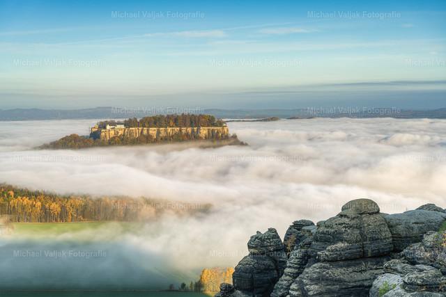Festung Königstein über dem Nebelmeer   Blick vom Pfaffenstein zur Festung Königstein im Elbsandsteingebirge, die sich an einem Morgen im Herbst aus dem Nebel erhebt.