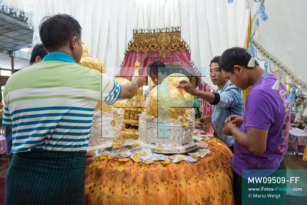 MW09509-FF | Myanmar | Nyaung Shwe | Reportage: Phaung Daw U Fest | Ein Dorfkloster während des Festivals auf dem Inle-See. Nur die Männer dürfen Goldplättchen den vier Buddha-Statuen spenden. Durch das jahrzehntelange Auftragen von Blattgold erkennt man nur schwer die eigentliche Form der Buddhas.   ** Feindaten bitte anfragen bei Mario Weigt Photography, info@asia-stories.com **
