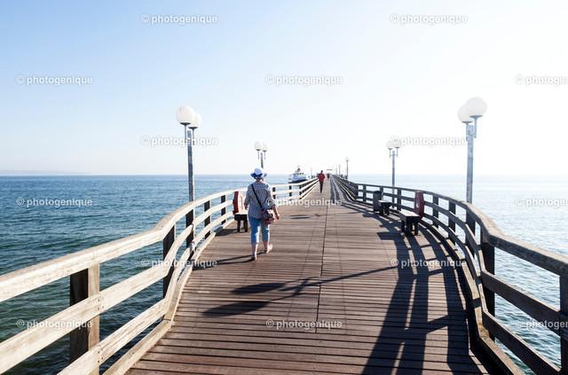 Auf der Seebrücke im Ostseebad Binz   Eine Frau mit Sonnenhut geht über die Seebrücke im Ostseebad Binz