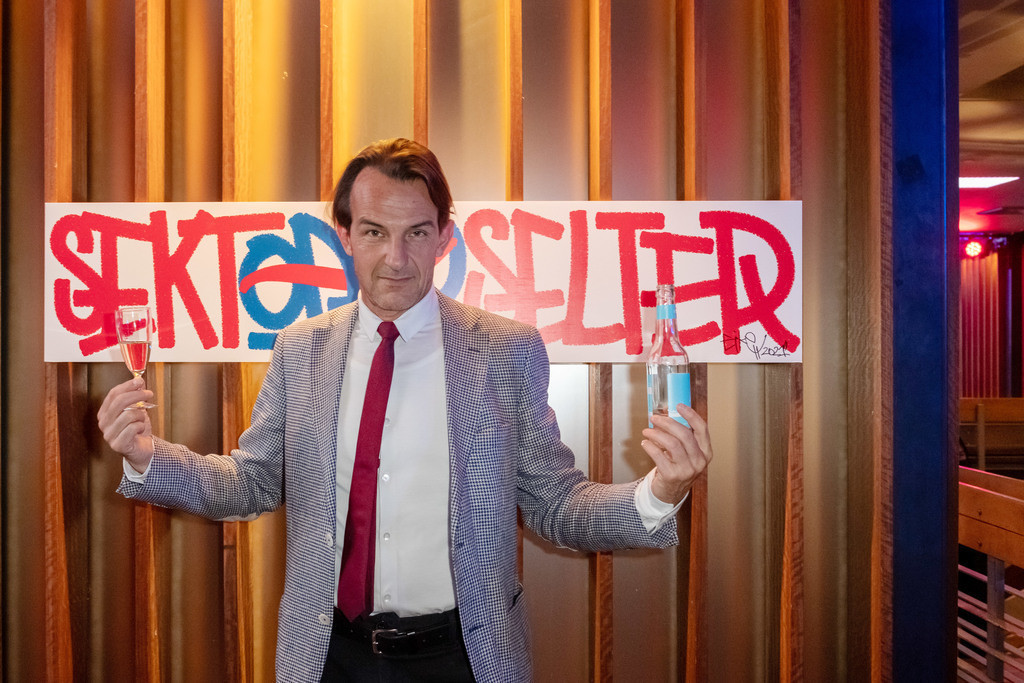 Sekt oder Selters - Art Parade by Getraenke Hoffmann | Schauspieler Hans Werner Meyer vor dem Entwurf von Eike Wendland, der den 7. Platz belegte.