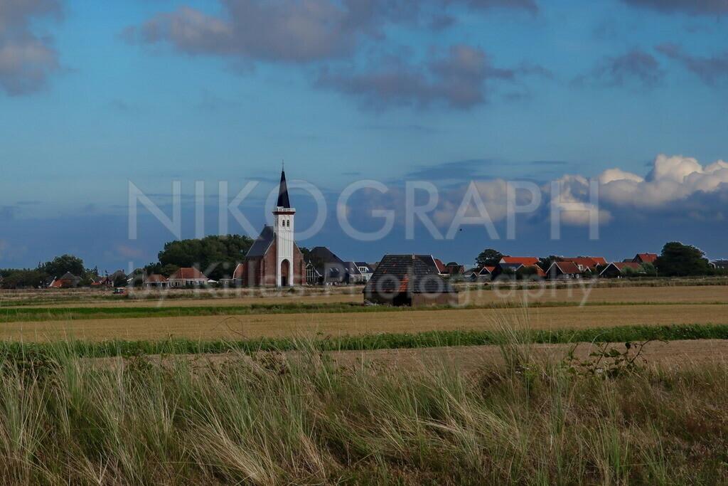 Den Hoorn | Die markante Kirche mit dem weißen Turm ist das Wahrzeichen des Dorfes Den Hoorn auf der Nordseeinsel Texel. Im Vordergrund ist eine der typischen Schafscheunen von Texel zu sehen. Die Schafscheunen bieten den Schafen Schutz Wind und Wetter, der Eingang ist entgegen der Hauptwindrichtung ausgerichtet.