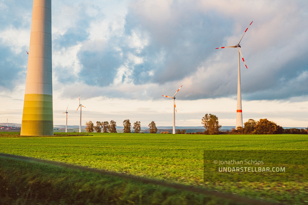Mensch, Klima! | ecological renewable green energy wind power station on a field in evening sun