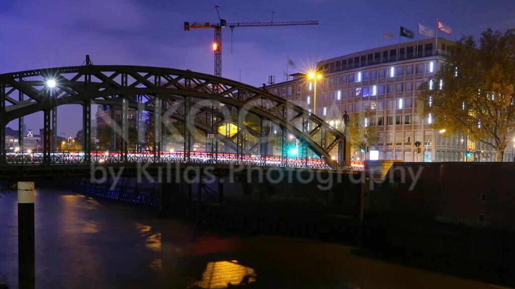 Brooksbrücke in Hamburg | Fahrzeuge ziehen auf der Brooksbrücke in Hamburg Lichtspuren in die Nacht. Ein Kran streckt sich im Nachthimmel empor.