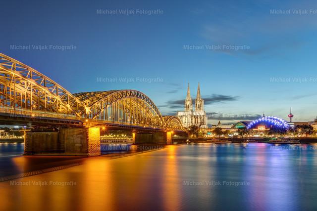 Köln Skyline | Blick auf die Skyline von Köln am Abend mit der beleuchteten Hohenzollernbrücke, dem Kölner Dom, Musicaldome und im Hintergrund dem Kölner Fernsehturm.