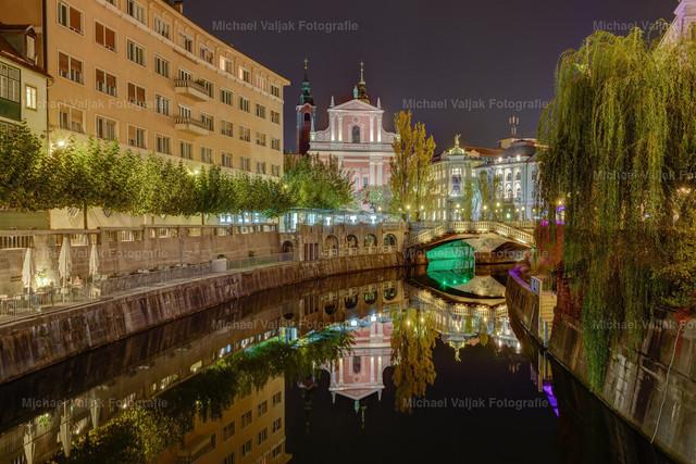 Ljubljana bei Nacht | Blick in Richtung Tromostovje (auf deutsch: Drei Brücken) und der Franziskanerkirche, zwei Wahrzeichen der Stadt. An diesem Abend war es vollkommen windstill, sodass es eine perfekte Spiegelung im Fluss Ljubljanica gab.