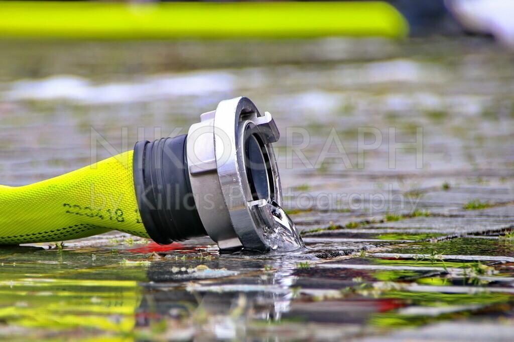 Feuerwehrlöschschlauch | Ein Löschschlauch in einer Wasserlache nach einer Feuerwehrübung.
