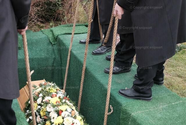 Sarg wird ins Grab abgelassen | Detail von einem offenen, abgedeckten Grab beim Herunterlassen des Sargs.