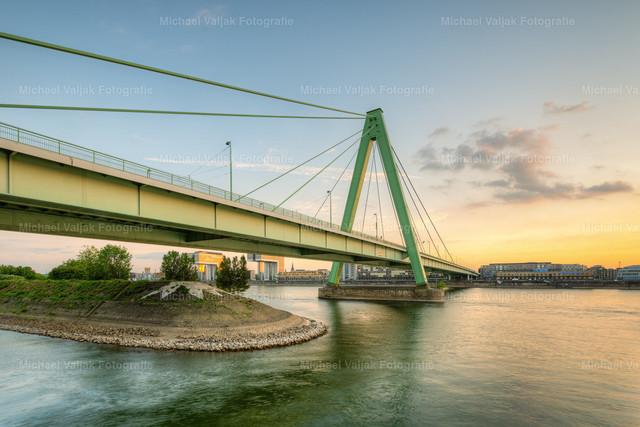 Severinsbrücke in Köln   Blick von der Rheinpromenade zur Severinsbrücke bei Sonnenuntergang. Links im Hintergrund sind zwei der drei Kranhäuser zu sehen.