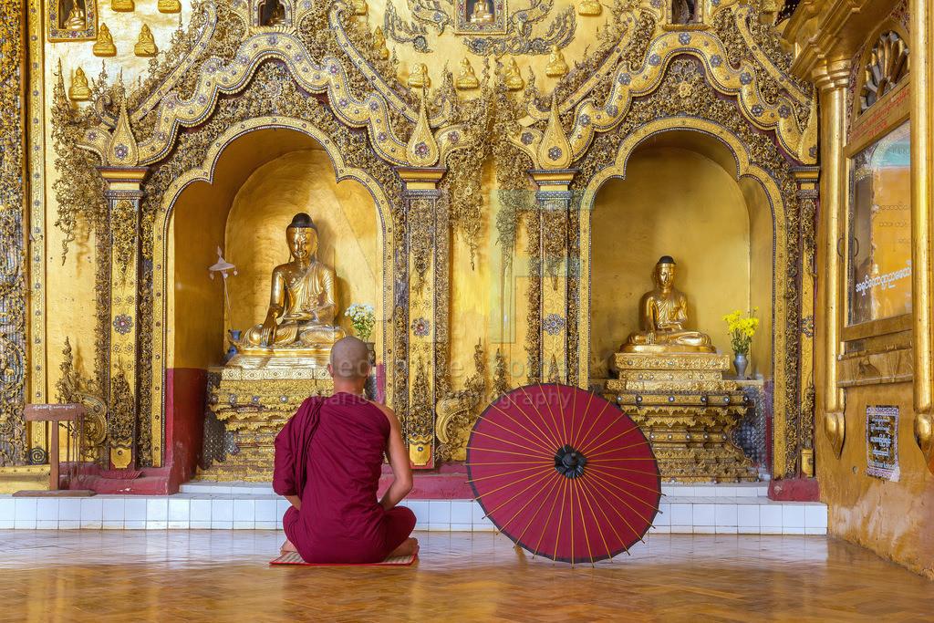 MW1119-0723 | Fotoserie DER ROTE SCHIRM | Meditierender Mönch vor goldenen Buddha-Statuen in einem buddhistischen Kloster am Inle-See in Myanmar