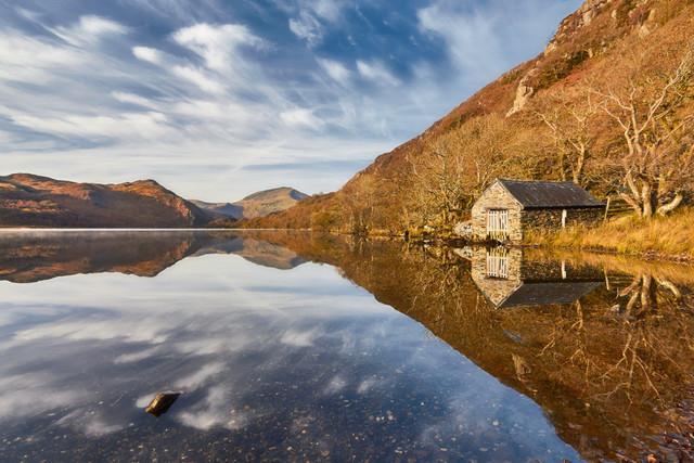 Haus am See | Ein Herbststurm hatte hier im Norden von Wales vor einigen Tage das meiste Laub von den Bäumen gefegt. Angesichts der totalen Stille an diesem Morgen war das kaum vorstellbar. Die fluffigen Wolken spiegelten sich im See und der blaue Himmel bildeten ein schönen Kontrast zum herbstlich gefärbten Ufer.