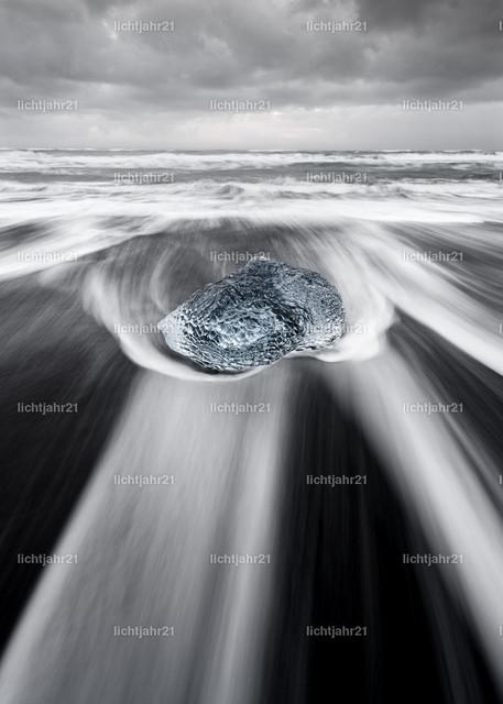 Eisblock in der Brandung | Runder Eisblock in blauen Farbtönen an einem Strand mit starker Brandung, die Wasserbewegung ist zu sehen (Langzeitbelichtung, deutliche Bewegungsspuren), darüber ein kontrastreicher grau bewölkter Himmel - Location: Island, Jökulsarlon (Jökulsárlón)