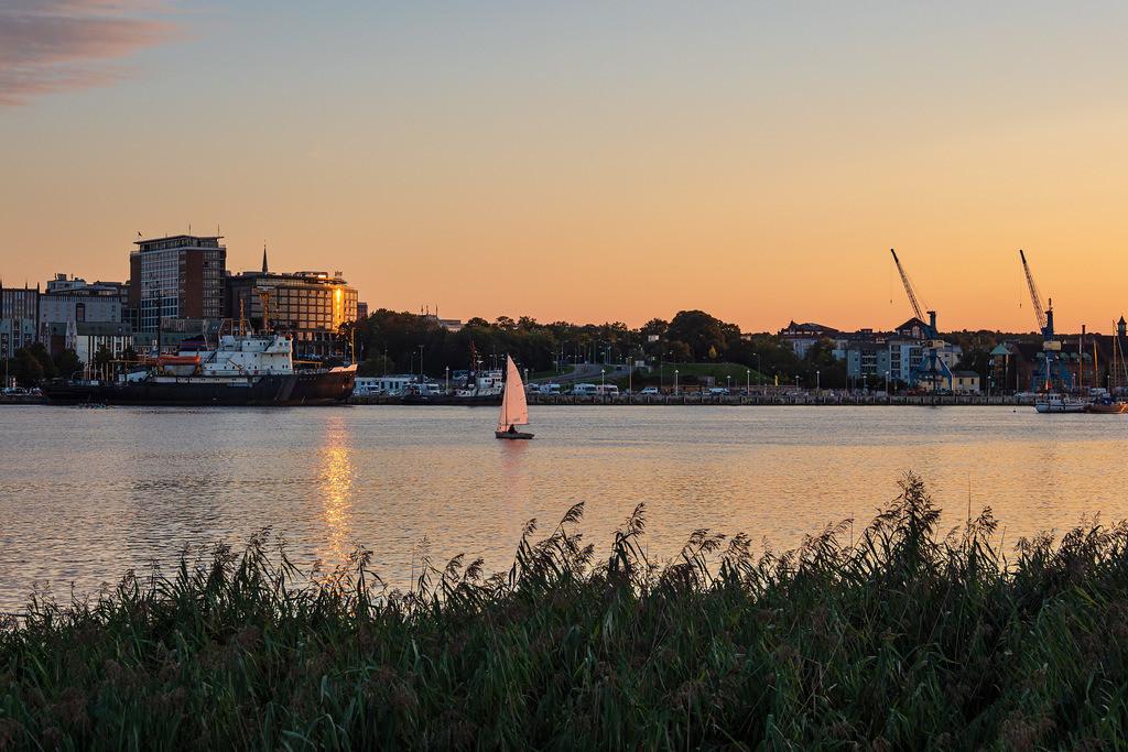 Blick über die Warnow auf die Hansestadt Rostock mit Segelboot | Blick über die Warnow auf die Hansestadt Rostock mit Segelboot.