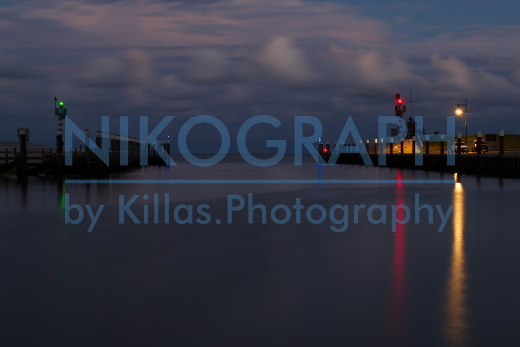 Hafenausfahrt von Oudeschild | Nachtaufnahme der Hafenausfahrt von Oudeschild. Das Abendrot der Sonne glüht in den Wolken über der Nordsee noch etwas nach. Die Hafenbeleuchtung spiegelt sich im Wasser.  Oudeschild ist der drittgrößte Ort der Gemeinde Texel. Neben dem Fischereihafen gibt es im Hafen von Oudeschild auch eine Marina.