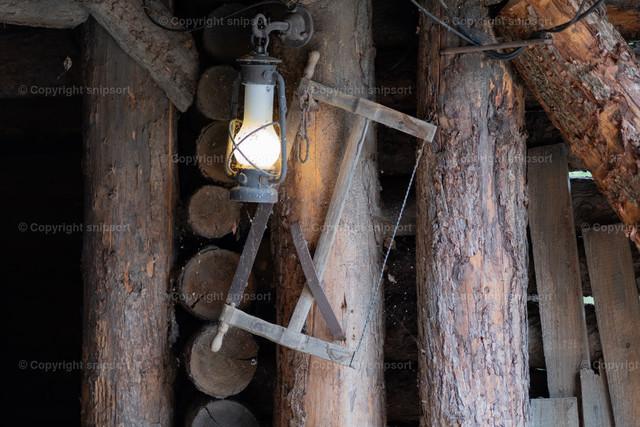 Alte Handsäge | Detail einer Werkstatt mit einer alten Holzhandsäge und einer Öllampe.