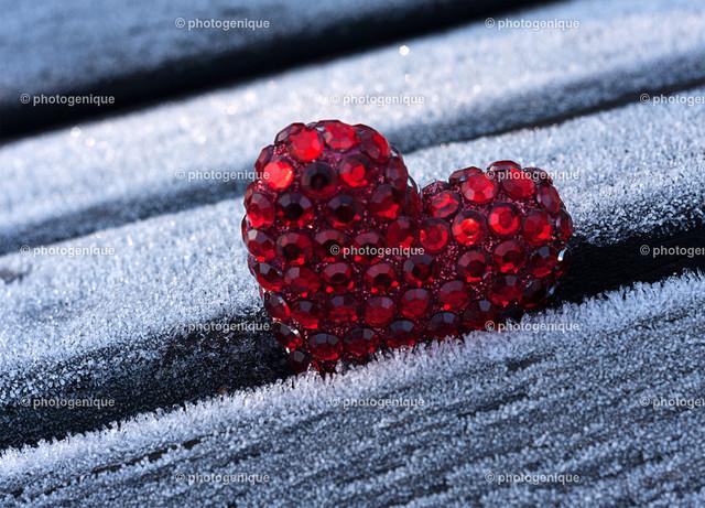 rotes Glitzerherz auf Eis   ein rotes Glitzerherz steckt zwischen zwei Balken, die mit Eiskristallen überzogen sind bei Tageslicht