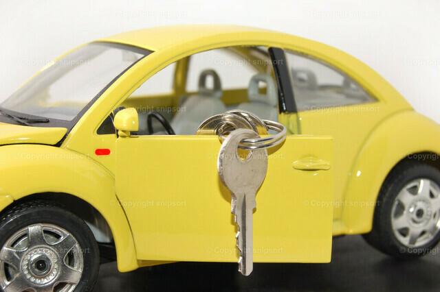Konzept bestandene Führerscheinprüfung | An der Tür von einem gelben Modellauto befestigte Autoschlüssel als Konzept für eine bestandene Führerscheinprüfung.