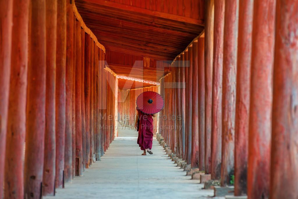 MW1119-2612 | Fotoserie DER ROTE SCHIRM | Buddhistischer Mönch im roten Säulengang aus Teakholz in Salay