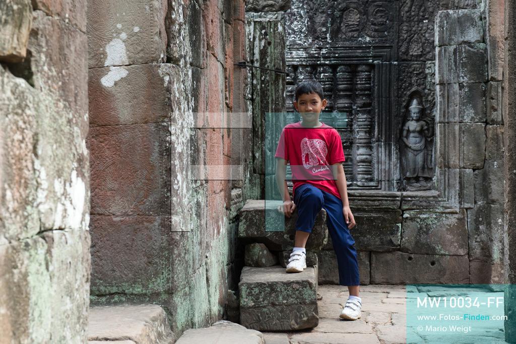 MW10034-FF | Kambodscha | Siem Reap | Reportage: Sombath erkundet Angkor | Sombath im Tempel Banteay Kdei.  Der achtjährige Sombath lebt in Kambodscha im Dorf Anjan, sechs Kilometer westlich von Siem Reap entfernt. In seiner Freizeit nimmt ihn manchmal sein Onkel in die berühmte Tempelanlage von Angkor mit. Besonders mag er die riesigen Wurzeln der Kapokbäume, die auf den alten Mauern wachsen. Seine Lieblingstempel in Angkor sind Ta Prohm, Banteay Kdei und Preah Khan.  ** Feindaten bitte anfragen bei Mario Weigt Photography, info@asia-stories.com **