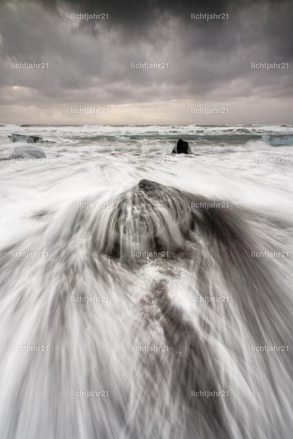 Eisblock mit Welle | Ein Eisblock wird an einem Strand schwarzen mit starker Brandung von einer Welle überspült, die Wasserbewegung ist zu sehen (Langzeitbelichtung, deutliche Bewegungsspuren), darüber ein kontrastreicher grau bewölkter Himmel - Location: Island, Jökulsarlon (Jökulsárlón)