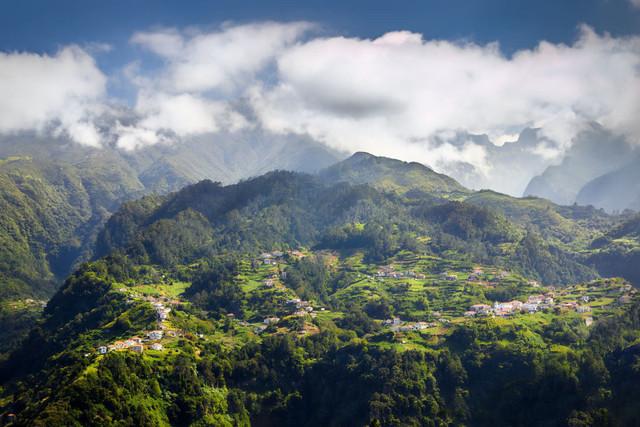 Grüne Berglandschaft auf Madeira | Die unzugängliche Berglandschaft Madeiras ist per se nur schwer erschließbar. Doch meist findet sich ein Weg, Häuser und Straßen anzulegen. Die Siedlung krallt sich förmlich an die grünen und steilen Berghänge, während die Wolken um die Gipfel ziehen.