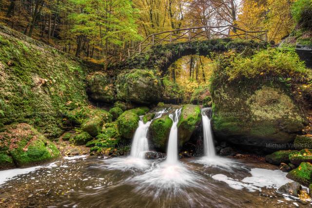 Schiessentümpel in Luxemburg #2 | Herbstliche Aufnahme des kleinen malerischen Schiessentümpel-Wasserfalls in der Region Müllerthal in Luxemburg. Das Wasser der Schwarzen Ernz schießt in drei Strömen über eine Felskante in ein darunter liegendes Wasserbecken und verläuft dann in Richtung der Ortschaft Müllerthal weiter. Er ist zusammen mit der idyllischen Brücke aus Stein und Holz, den umliegenden Felsen und der üppigen Vegetation zu einem der beliebtesten Ausflugsziele in der Region Müllerthal geworden (auch Kleine Luxemburger Schweiz genannt).