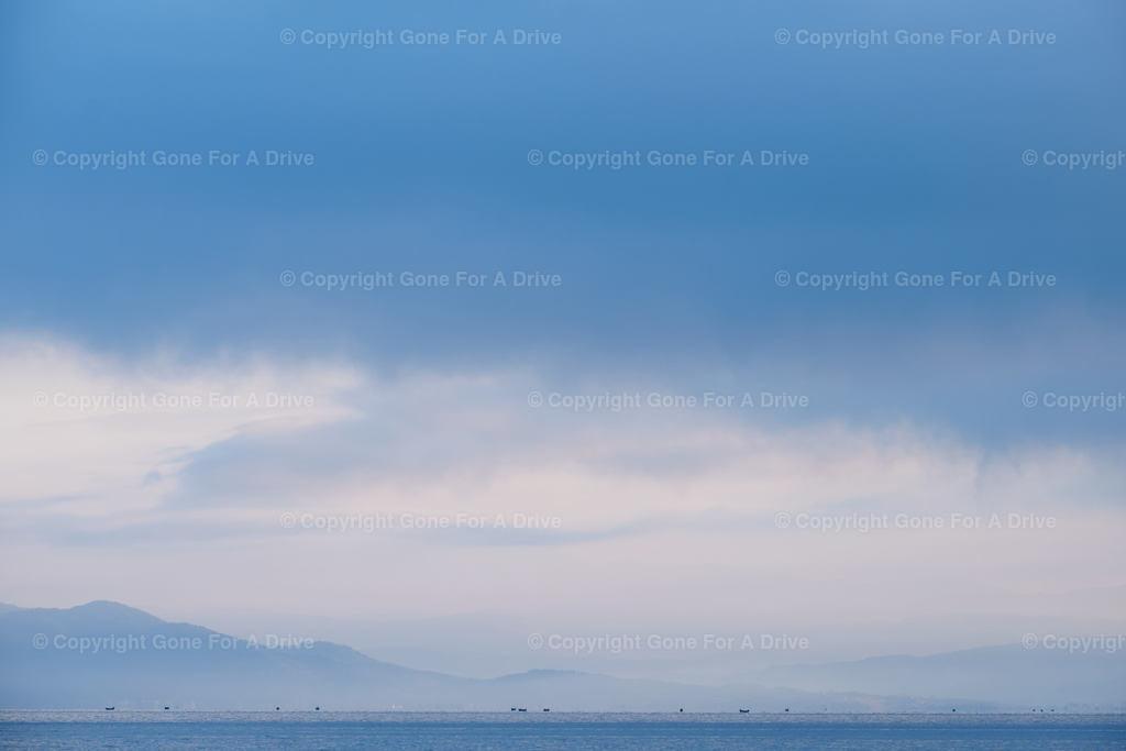 Albanien | Silhoutten von Fischerbooten am Horizont auf dem Ohridsee