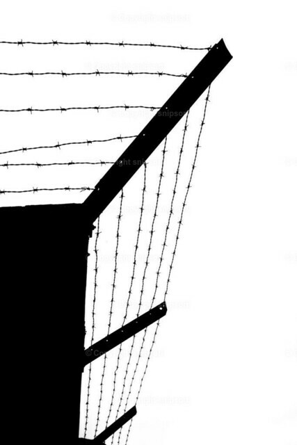 Gefängnismauer mit Stacheldraht | Silhoette von mehreren Schichten Stacheldraht auf einer Gefängnismauer