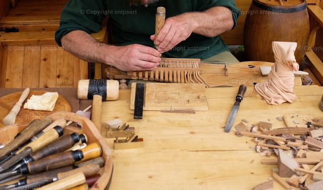 Instrumentenbauer bei der Arbeit | Ein Instrumentenmacher beim Anfertigen von Musikinstrumenten aus Holz