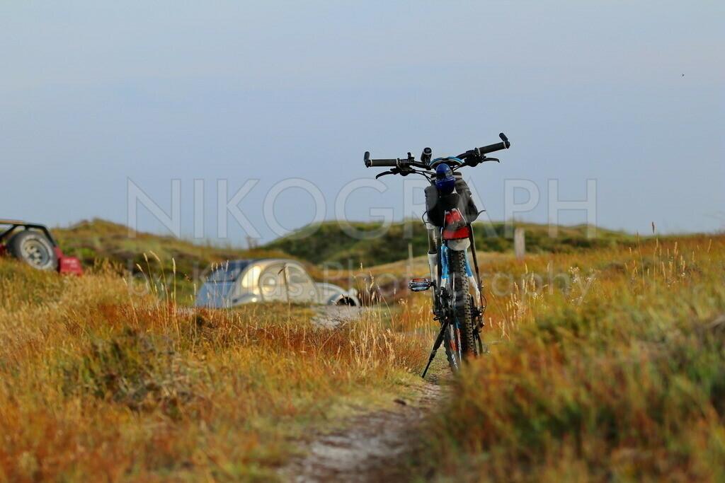 Fahrrad in den Dünen | Ein Fahrrad in den Dünen von Texel. Auf dem Parkplatz im Hintergrund ist eine Ente geparkt.