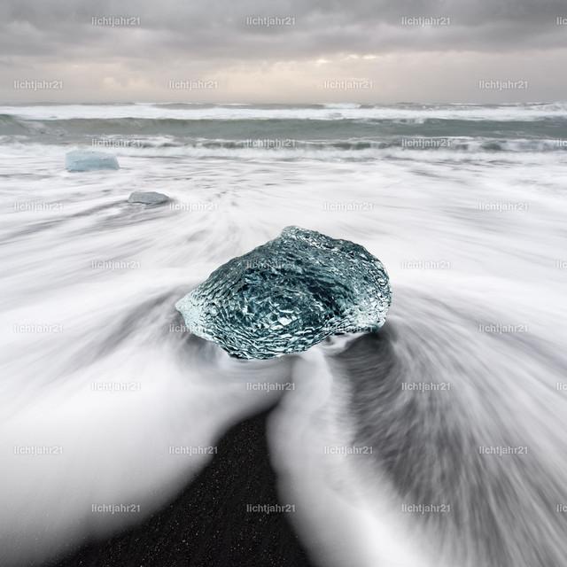 Eisblock am schwarzen Strand | Runder Eisblock in blauen Farbtönen an einem Strand mit starker Brandung, das zurückfließende Wasser zeigt ein markantes Muster und Bewegungsspuren (Langzeitbelichtung), darüber ein bewölkter Himmel mit teilweise hellen gelben Farbtönen, Tiefenwirkung - Location: Island, Jökulsarlon (Jökulsárlón)