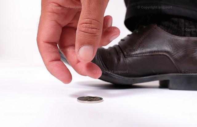 Mann findet eine Münze | Ein Mann hebt verstohlen eine auf dem Boden liegende Münze auf.