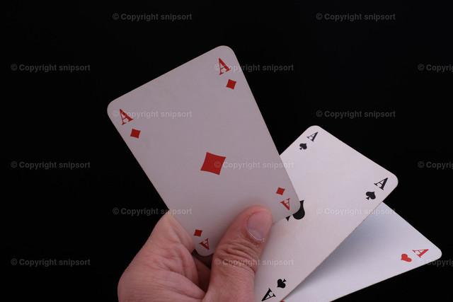 Drei Asse in der Hand über einem schwarzen Hintergrund | Eine männliche Hand hält drei Asse über schwarzem Hintergrund