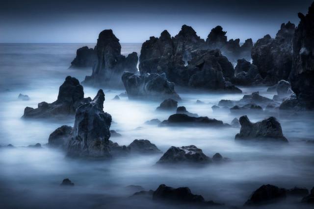 Rising Black | Es muss natürlich nicht immer ein Sonnenuntergang sein, um ein harmonisches Bild zu erhalten. Eine halbe Stunde danach taucht die Blaue Stunde die Landschaft in ein letztes, kühles Licht. Die dunklen Lavafelsen der Westküste von Lanzarote ragen dabei gespenstisch aus dem Meer hervor.