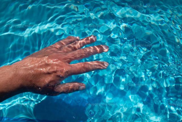 Hand im Pool | Ein Mann taucht die Hand in kristallblaues Wasser des Swimmingpools ein.