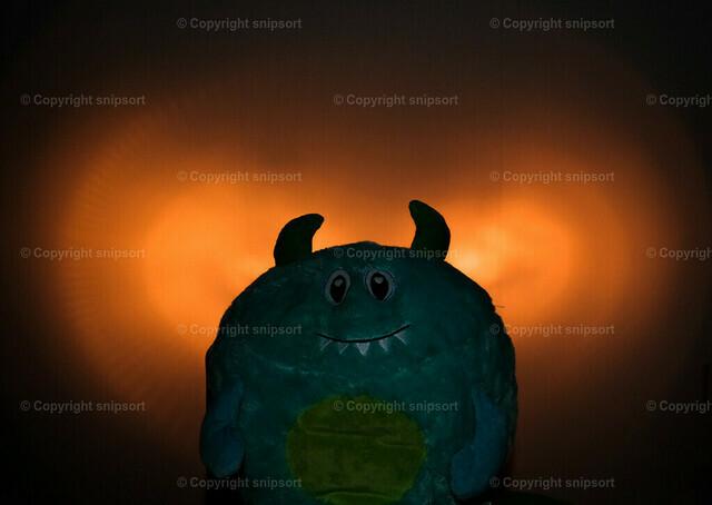 Spielzeugteufel | Ein Kuscheltier in Form eines Teufels mit feueriger Aura im Hintergrund.