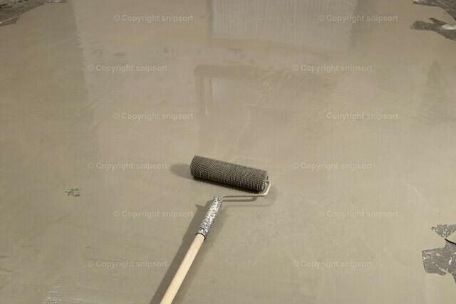Bodenausgleichsmasse | Detail von einer Stachelrolle mit ausgekippter Bodennivelliermasse