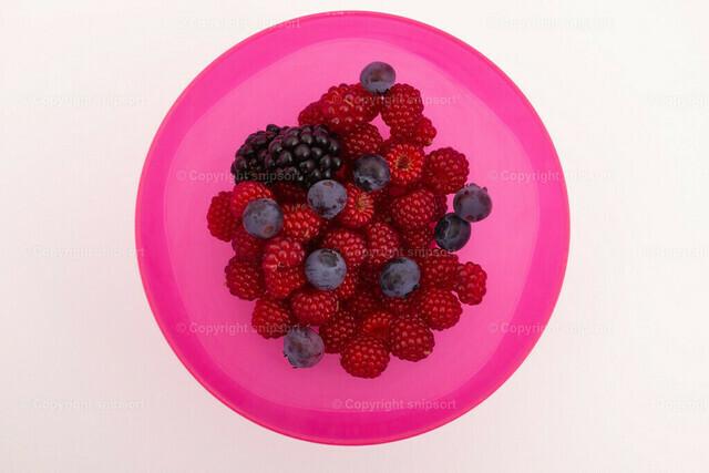 Schale mit Beeren | Eine rote Schale mit frisch gepflückten Gartenbeeren.
