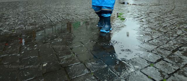 Kind in der Pfütze | Ein Kleinkind mit blauen Gummistiefeln und einem blauen Regenmantel läuft durch eine Pfütze.