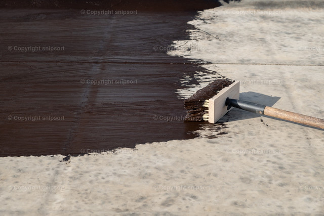 Streichen eines Flachdachs mit Bitumenmasse