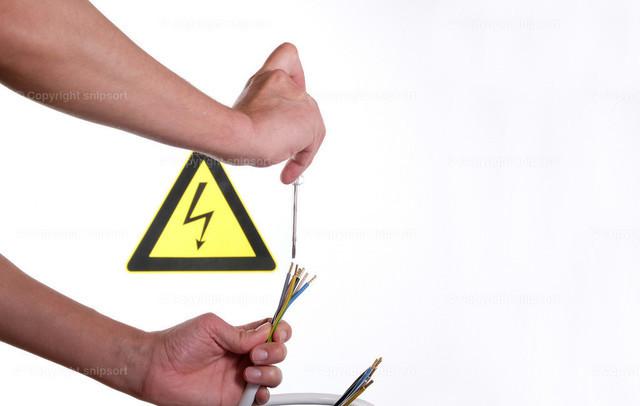 Prüfung der Drähte auf Leitfähigkeit | Ein Mann prüft mit dem Indikator die Stromleitungen. Im Hintergrund ist ein Warnschild für Gefahr bei Strom.