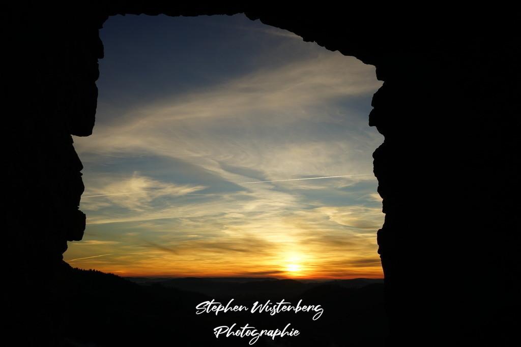 Sunset Burgruine Falkenstein | Blick durch eine Fensteröffnung der Burgruine Falkenstein auf das einen Sonnenuntergang über dem Donnersberger Land